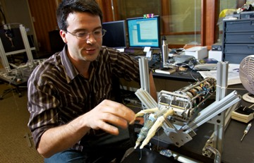 University of Washington doctoral student Eric Rombokas interacts with a lifelike robotic hand that includes the same number of muscles and tendons as the human hand, allowing the possibility for a more seamless integration with the human nervous system. The robotic hand was built in the UW