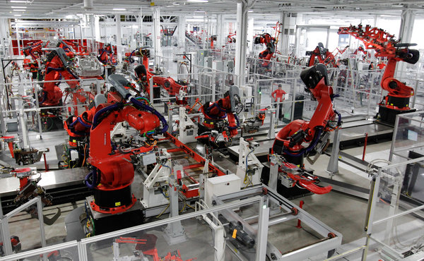 While the many robots in auto factories typically perform only one function, in the new Tesla factory in Fremont, Calif., a robot might do up to four: welding, riveting, bonding and installing a component [image courtesy Paul Sakuma/Associated Press via The New York Times].